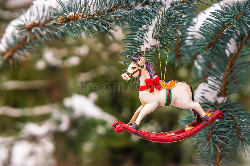 Rocking horse and snowy pine tree decorated for Christmas royalty free stock photo