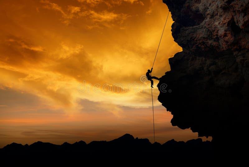 Rockklättrare på solnedgången royaltyfri fotografi