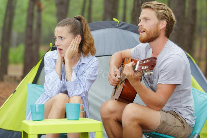 Rockman, das Gitarre und gebohrte Frau spielt stockfoto