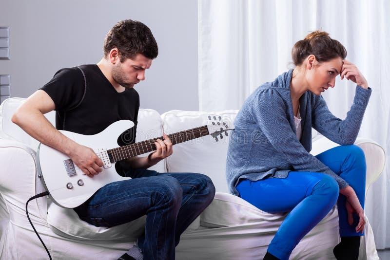 Rockman het spelen gitaar en bored vrouw stock fotografie