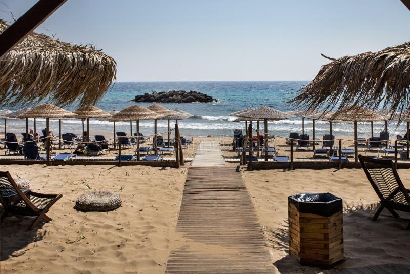Rockowa formacja w oceanie Tkany parasol, Nastawczy Plażowego krzesła Łóżkowy obszycie, Fałdowy i Wyjawiony morze Drewniana ścież zdjęcie stock