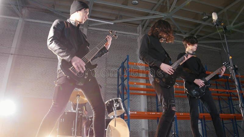 Rockowa grupa ma powtórkę Gitarzyści w czerni ubraniach bawić się ich dobosza na tle i części obraz stock