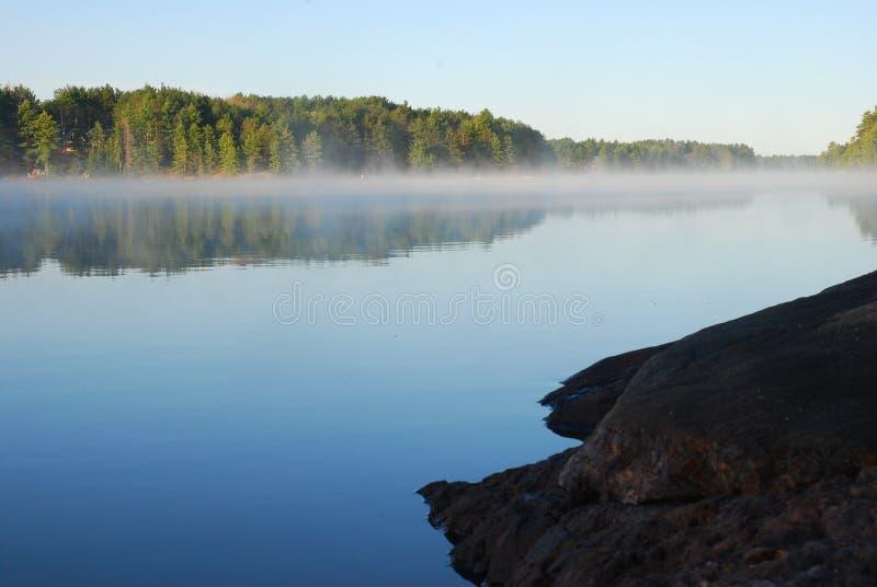 Rockowego wychodu czekanie na wschodzie słońca przy jeziorem obrazy royalty free