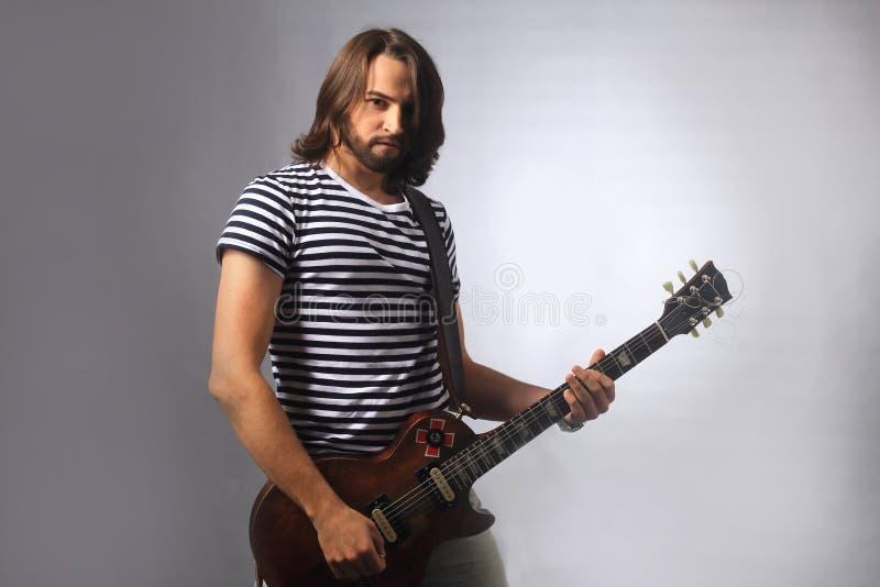 Rockowy muzyk bawić się sola na gitarze Fotografia na szarym tle zdjęcie royalty free