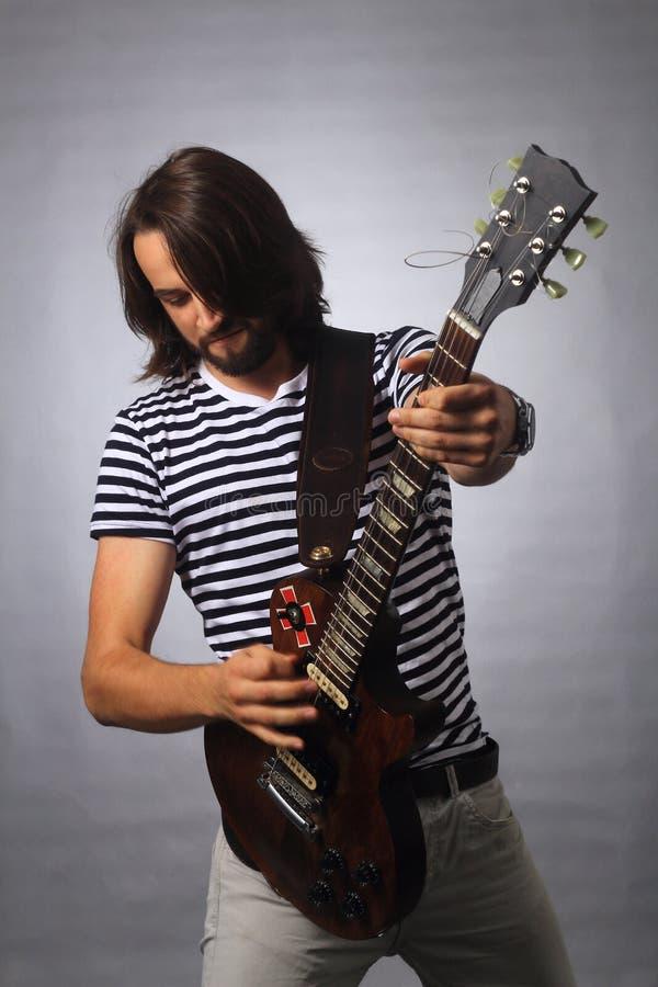 Rockowy muzyk bawić się sola na gitarze Fotografia na szarym tle fotografia royalty free