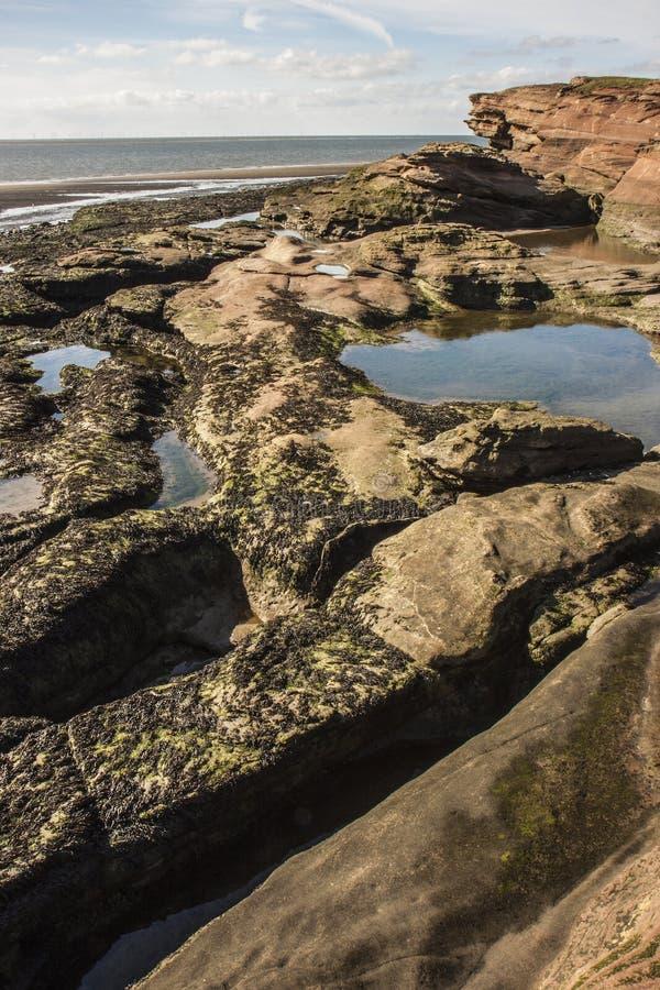 Rockpools e scogliera all'isola di Hilbre, Kirby ad ovest, Wirral immagine stock