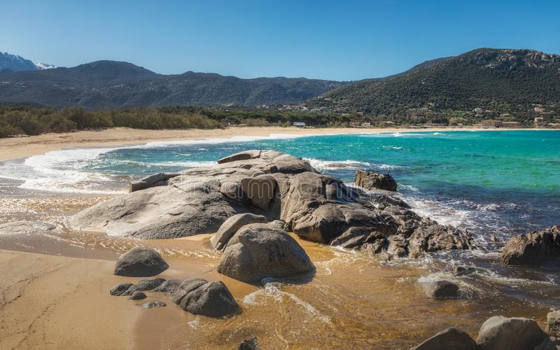 Rocks at Algajola beach in Balagne region of Corsica. Waves washing onto rocks and sand at Algajola beach in the Balagne region of Corsica under a deep blue sky stock images