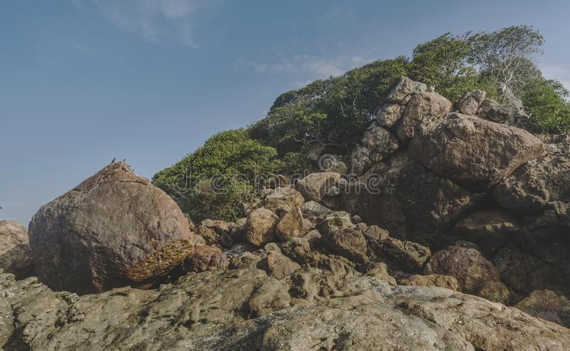 Rocks on bank at the beautiful tropical beach located at the island in ocean royalty free stock images