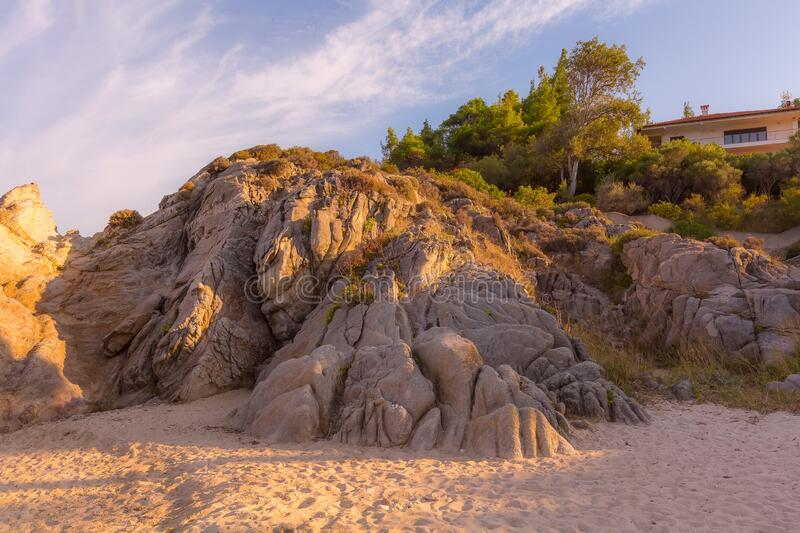 Rocks and beach in Vourvourou, Chalkidiki, Greece. Fava sandy beach, Vourvourou, Chalkidiki or Halkidiki, Greece summer sunset scenery, forest green mountains royalty free stock photo