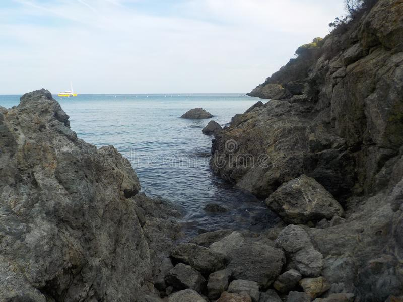 Rocks and blue sea with a distant yellow boat royalty free stock images