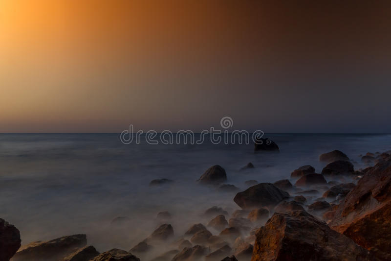 Rocks in a calm sea royalty free stock photography