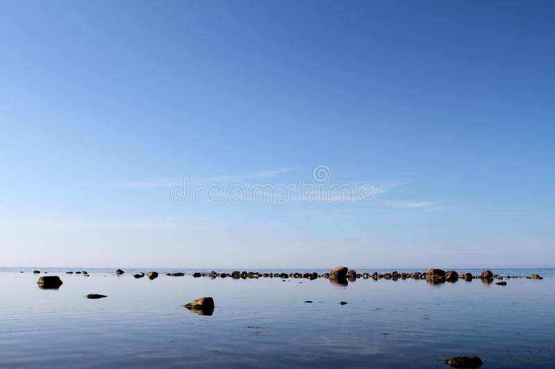 Rocks on calm waters. Calm water with rocks visible royalty free stock images