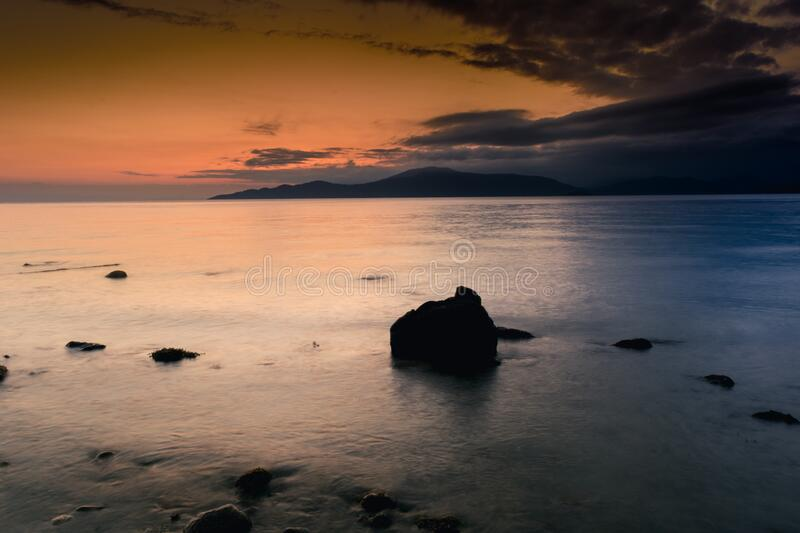 Rocks on coastline at sunset stock image