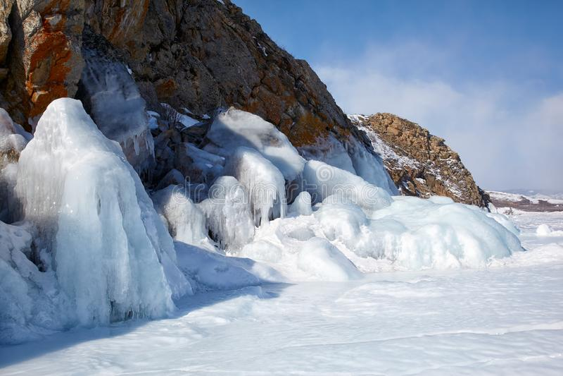Rocks covered by ice on winter siberian Baikail lake. Under blue sky backgroun royalty free stock photo