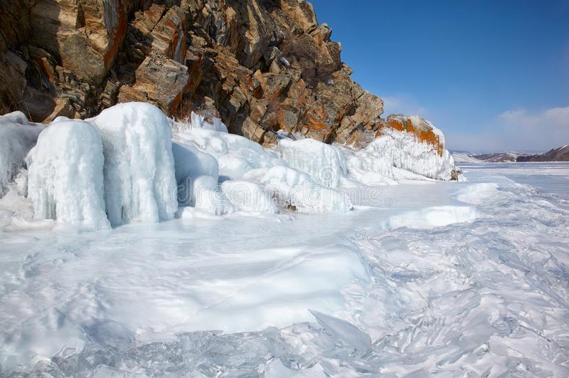 Rocks covered by ice on winter siberian Baikail lake. Under blue sky backgroun royalty free stock photography