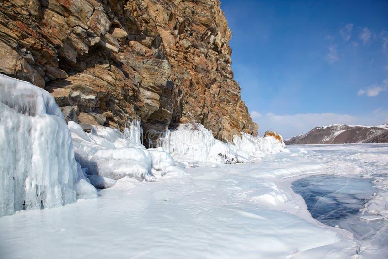 Rocks covered by ice on winter siberian Baikail lake. Under blue sky backgroun stock photo