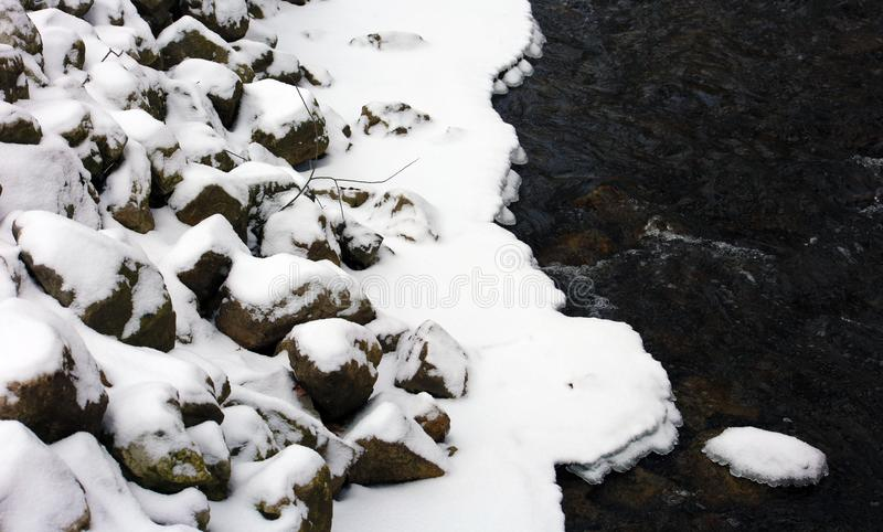 Rocks covered with snow in cold river after winter storm royalty free stock photo