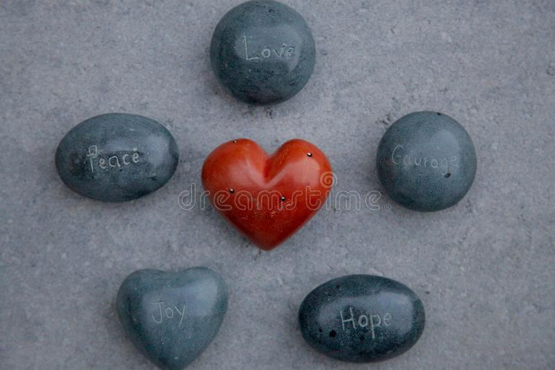 Rocks engraved with words Love, Peace, Courage, Hope, Joy surrounding a red heart royalty free stock photos