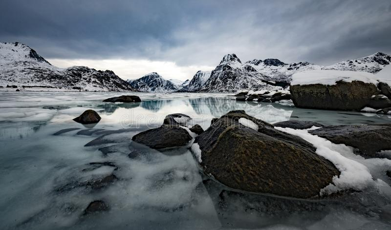 Rocks in a frozen mountain lake with snowy mountains reflecting royalty free stock photography