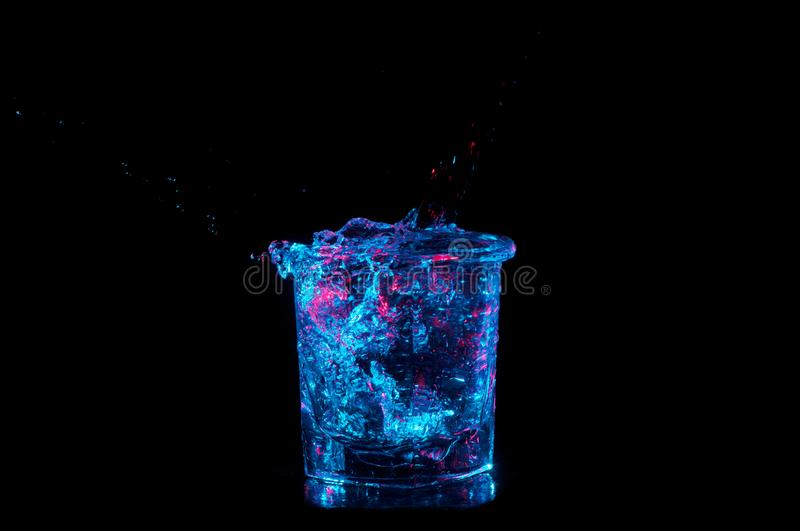 Rocks glass overflowing with water under bright blue lights with red on a black background royalty free stock images