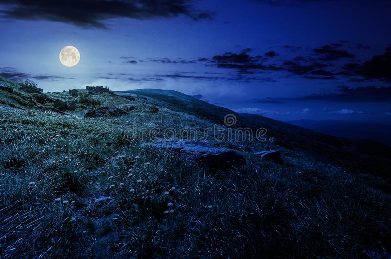 Rocks on grassy hillside of the mountain at night stock image