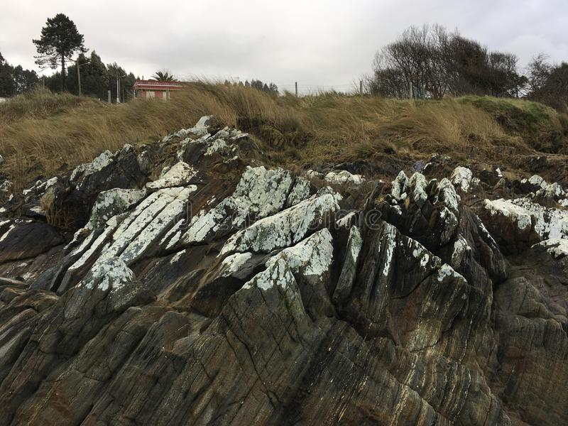 Rocks with lichens entering the beach, Galicia, Spain stock image