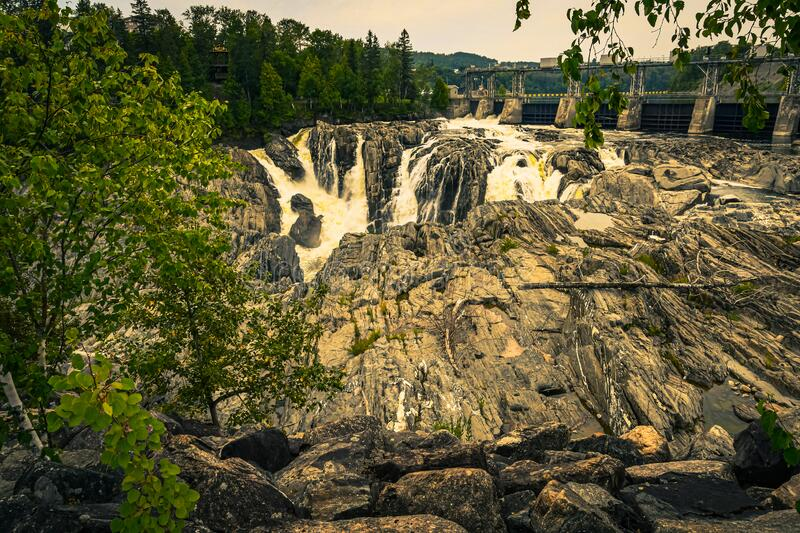 Rocks, Logs, Textures and a Dam on the St John. View of the dam on the Saint John River below the Grand Falls waterfall in New Brunswick, Canada, as it flows stock photo