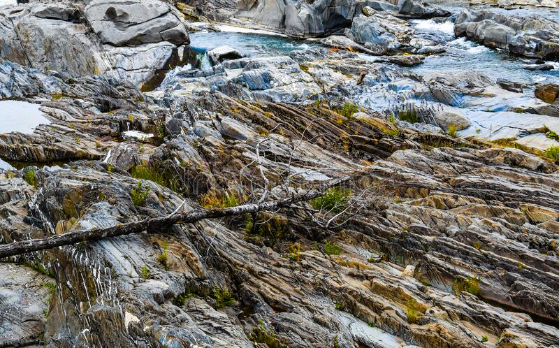 Rocks, Logs, Textures Beside a Waterfall. View of  the Saint John River below the Grand Falls waterfall in New Brunswick, Canada, as it flows over eroding rock royalty free stock images