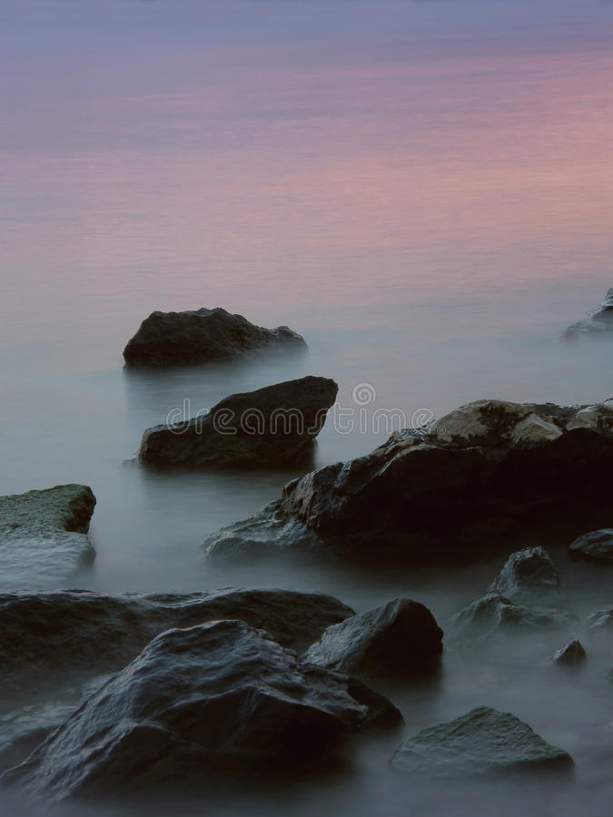 Rocks in the misty sea in sunset royalty free stock photography