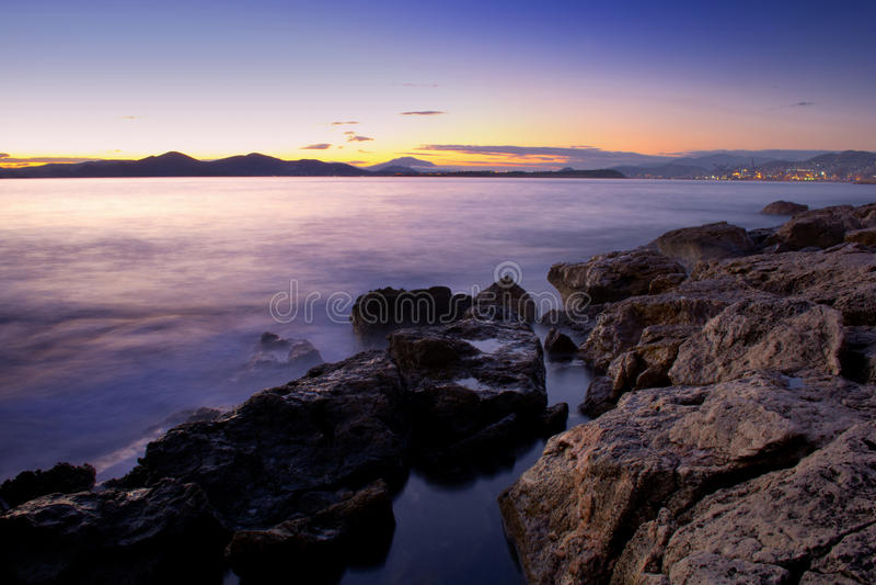 Rocks in the misty sea in sunset stock photo