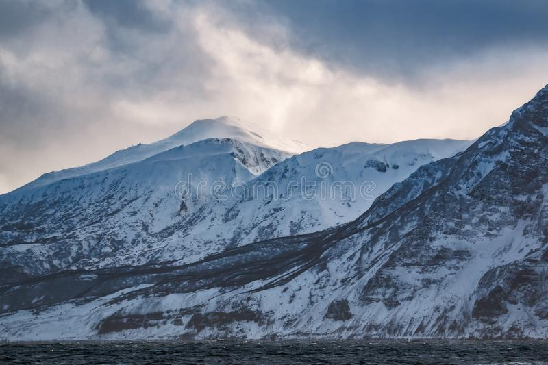 Rocky coast of one of the Kuril Islands in the winter during a snow storm royalty free stock photos