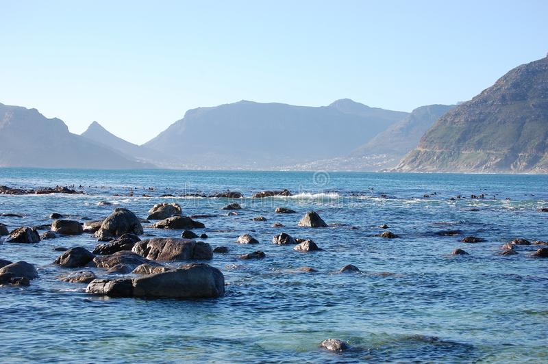 Rocks in the ocean,  Table Mountain,  Cape Town South Africa. Nature, scenic, wildlife, landscape, waterfront, sky royalty free stock photos