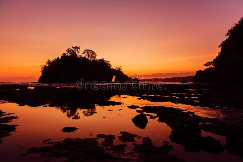 Rocks in ocean and bright sunset at beach, Nusa Penida stock image
