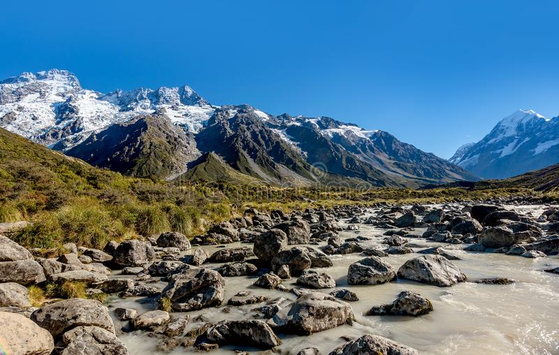 Rocks, river and snowy mountains in the background. Walking the royalty free stock image
