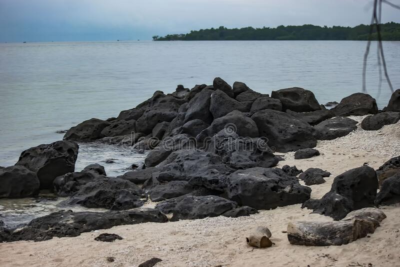 The rocks on the sandy beach stock image