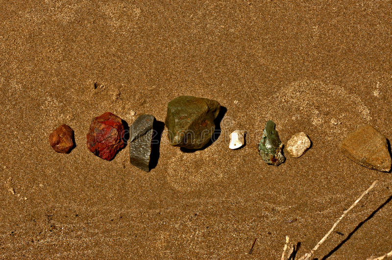 Rocks on the sandy beach stock image