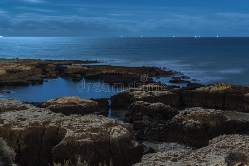 Rocks in a Sea. Rocks in the sea, with ships lights in the background on cloudy night royalty free stock images