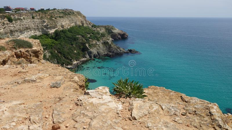 Rocks by the sea at Cape Fiolent. The turquoise color of the sea stock photography