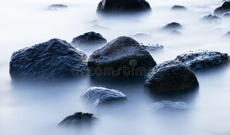 Rocks in sea long exposure stock image