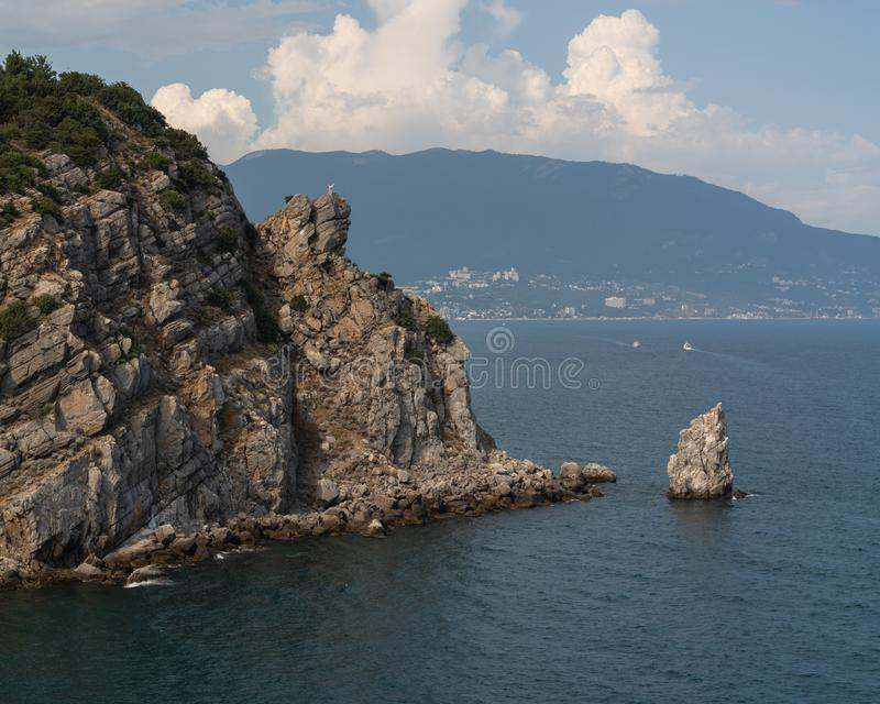 Rocks on the seashore. Mountains in the background. Nice sunny day. Forest at the top of the cliff. Clouds accumulated at the top of the cliff stock photography