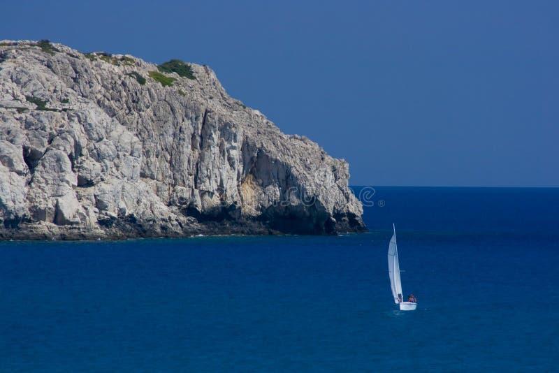 Rocks and small sailboat stock photography