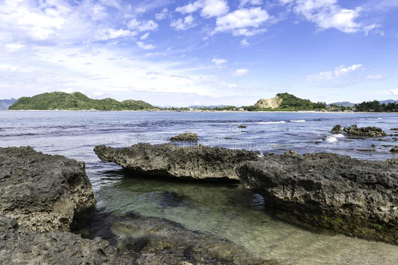 On the rocks, Small volcanic rocks in shallow clear sea water with tropical islands day. Small rocks stand out of the sea, the crystal clear tropical waters of stock image