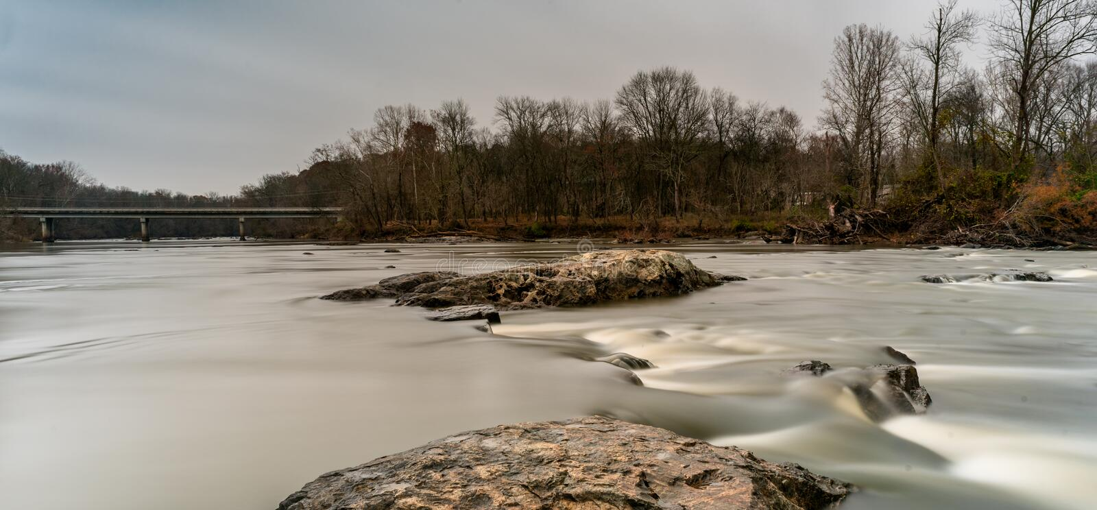 Rocks on a smooth Haw River with a highway bridge in the background. In North Carolina stock photography