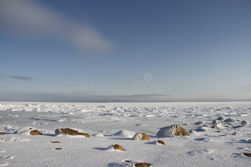 Rocks in the snow under a blue sky in the arctic, north of Arviat. Nunavut, Canada royalty free stock photos