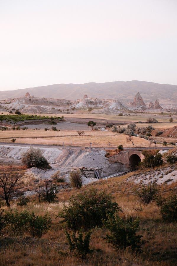 Rocks som ser som champinjoner t?nde dramatiskt, vid en solnedg?ng i Cappadocia, Turkiet arkivfoto