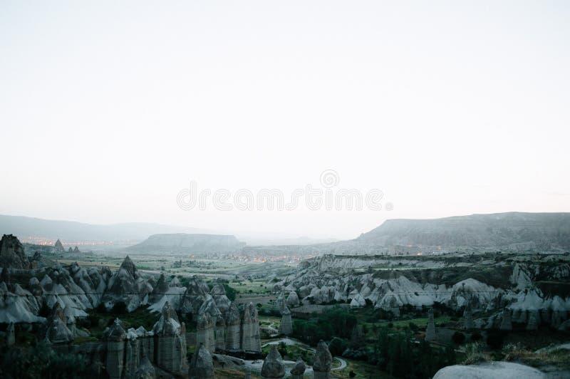 Rocks som ser som champinjoner t?nde dramatiskt, vid en solnedg?ng i Cappadocia, Turkiet royaltyfria bilder