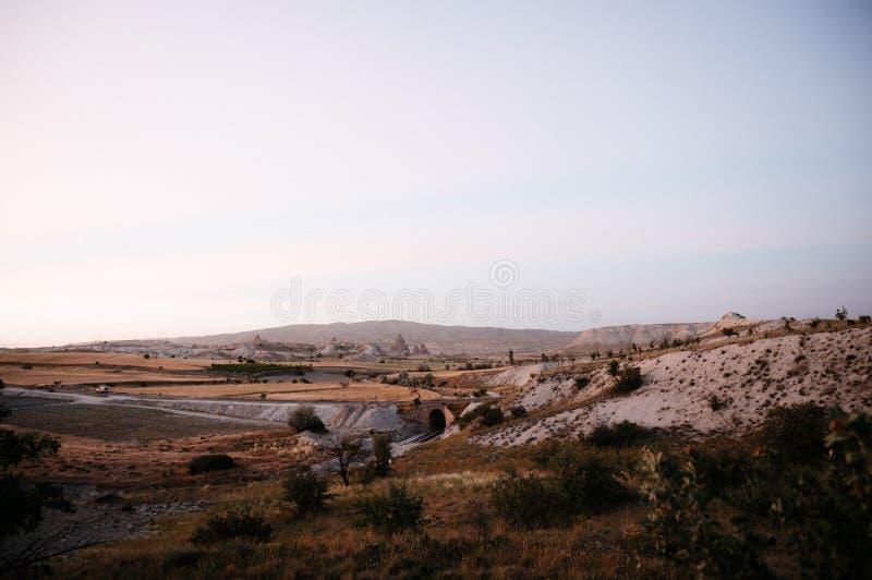 Rocks som ser som champinjoner t?nde dramatiskt, vid en solnedg?ng i Cappadocia, Turkiet arkivbild