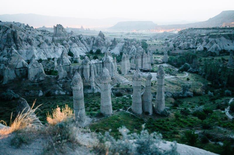 Rocks som ser som champinjoner t?nde dramatiskt, vid en solnedg?ng i Cappadocia, Turkiet arkivfoton