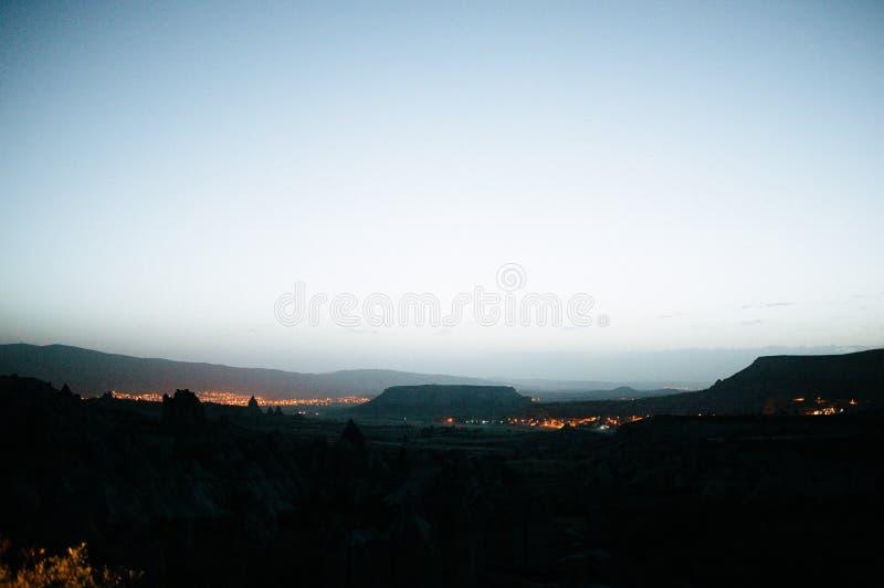 Rocks som ser som champinjoner t?nde dramatiskt, vid en solnedg?ng i Cappadocia, Turkiet fotografering för bildbyråer
