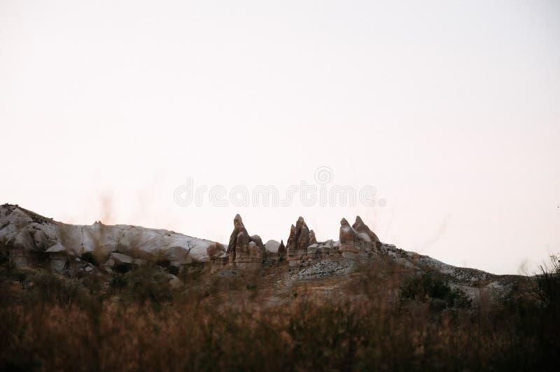 Rocks som ser som champinjoner t?nde dramatiskt, vid en solnedg?ng i Cappadocia, Turkiet royaltyfria foton